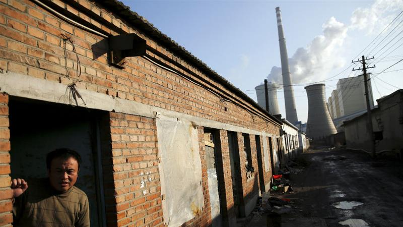 A migrant worker steps out of his accommodation in an area next to a coal-fired power plant in Beijing [File: Damir Sagolj/Reuters]