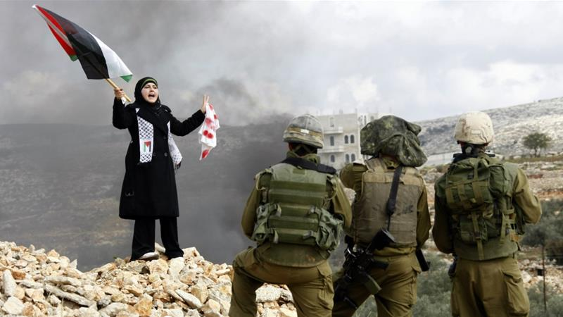 A Palestinian woman stands in front of Israeli soldiers during a protest in the West Bank village of Bilin near Ramallah against Israel's offensive in Gaza January 8, 2009 [Eric Gaillard/Reuters]