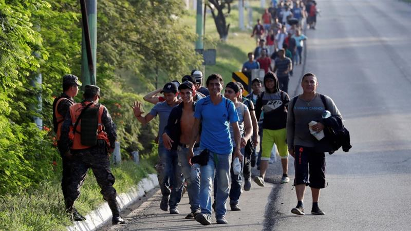 Central American migrants, part of a second wave of migrants heading to the US, walk along a highway as they continue their journey to the Mexican border, in Zacapa, Guatemala [Luis Echeverria/Reuters]