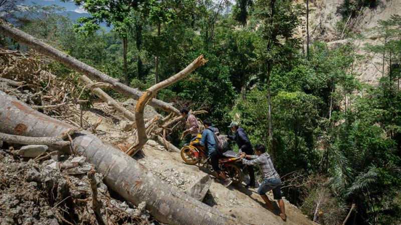 Motorcyclists attempt to cross landslide-damaged roads in Central Sulawesi [Ian Morse/Al Jazeera]