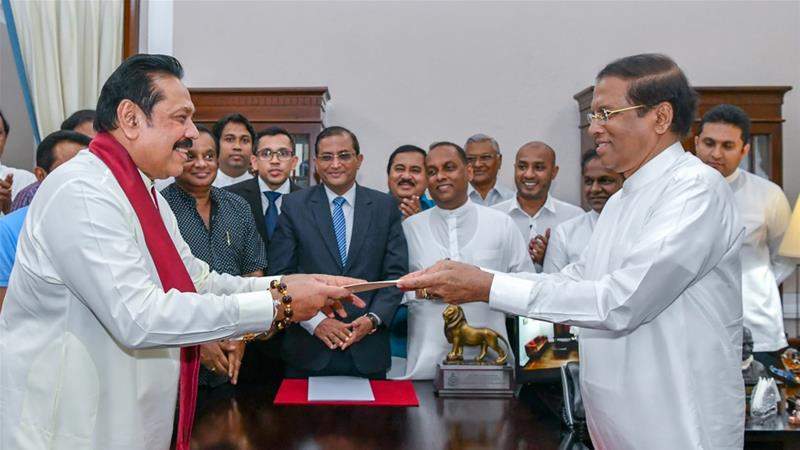 Maithripala Sirisena (right) appointed Mahinda Rajapaksa (left) at a rushed ceremony in Colombo [AFP]