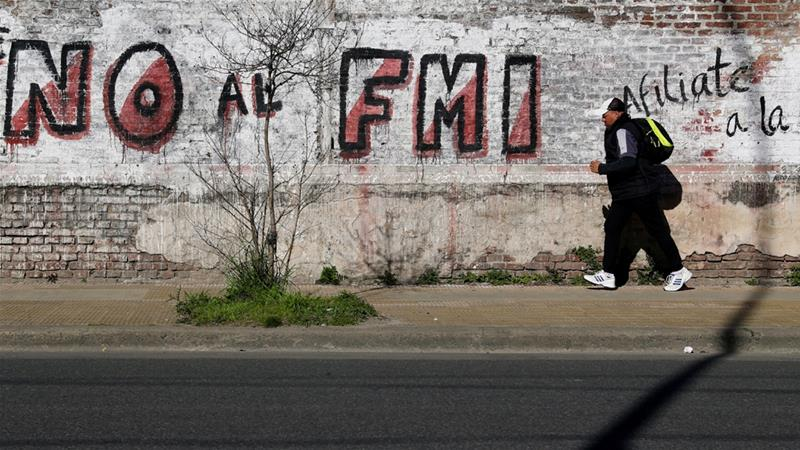 A man runs by a graffiti that reads 'No to the IMF (International Monetary Fund)' in Buenos Aires [Marcos Brindicci/Reuters]