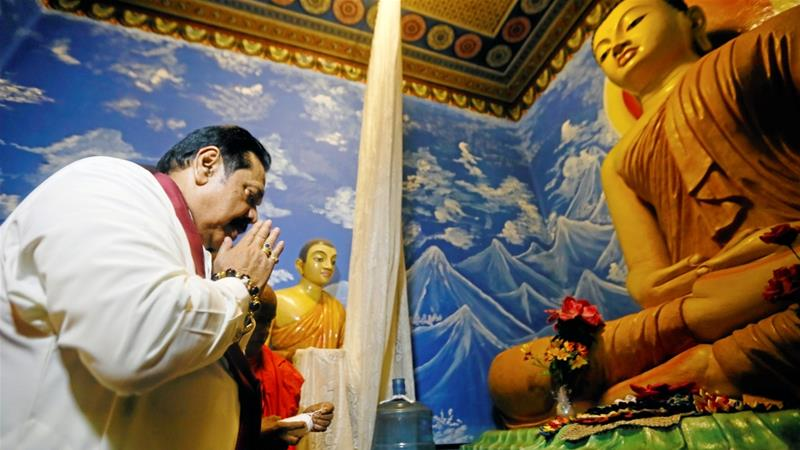 Rajapaksa prays at a Buddhist temple after being sworn in as the new PM in Colombo [Dinuka Liyanawatte/Reuters]