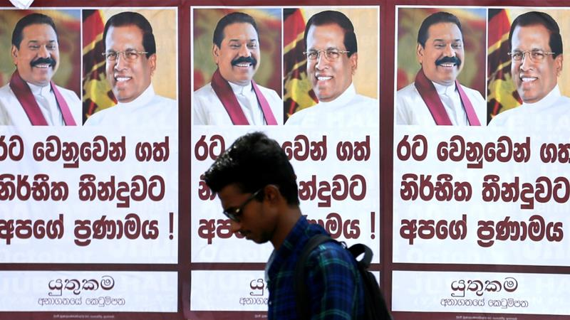 A man walks past a poster of Sri Lanka's newly appointed Prime Minister Mahinda Rajapaksa and President Maithripala Sirisena on a main road in Colombo, Sri Lanka October 28, 2018 [Reuters]