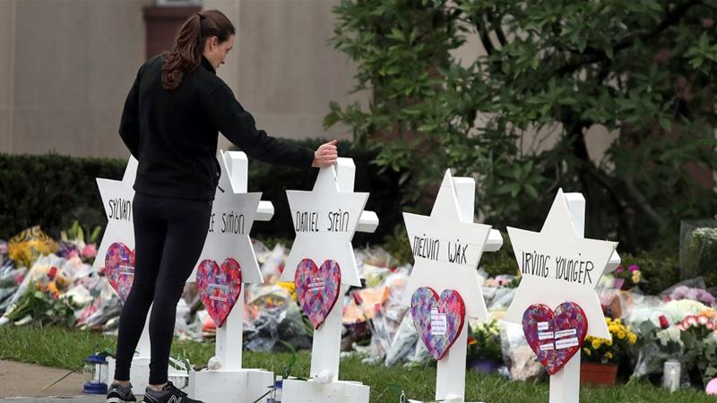 A woman pays respects at memorial outside the Tree of Life synagogue following Saturday's shooting [Cathal McNaughton/Reuters]