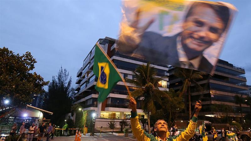 A supporter of Brazilian presidential candidate Jair Bolsonaro is seen in front of Bolsonaro''s condominium at Barra da Tijuca neighborhood in Rio de Janeiro [Sergio Moraes/Reuters]