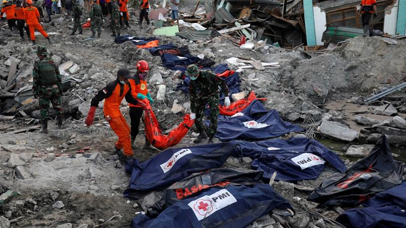 Soldiers and rescue workers carry the remains of recovered victims in Balaroa neighbourhood in Palu [Darren Whiteside/Reuters]