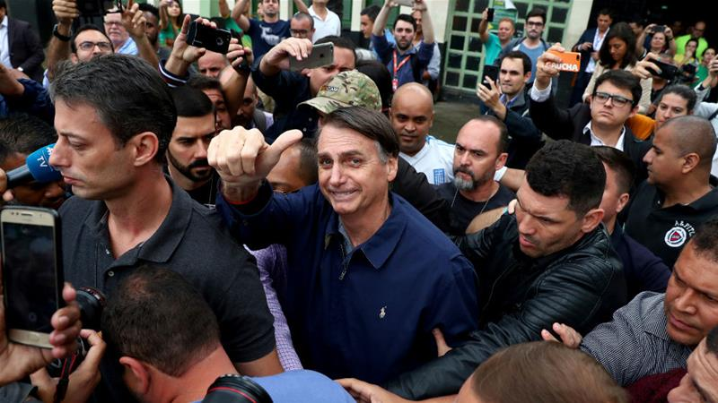 Far-right candidate Jair Bolsonaro gestures after casting his vote in the first round on October 7 [Pilar Olivares/Reuters]