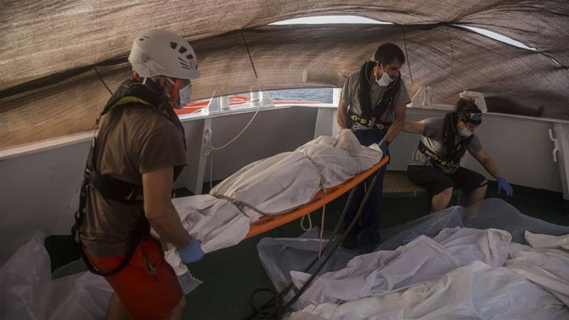 Aid workers recover the bodies of Sub-Saharan migrants in the Mediterranean Sea near Libya [Santi Palacios/AP Photo]