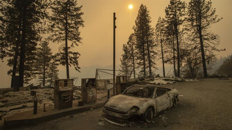 As the Camp Fire burns nearby, a scorched car rests by petrol pumps near Pulga, California [Noah Berger/AP Photo]