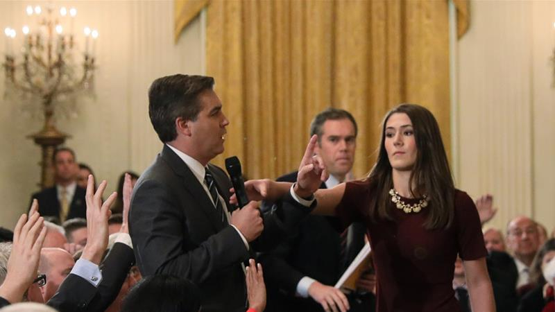 A White House intern reaches for and tries to take away the microphone held by CNN correspondent Jim Acosta [Jonathan Ernst/Reuters]
