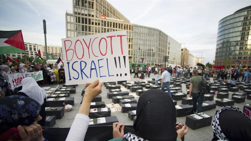 "A woman holds a sign which reads ""Boycott Israel"" in front of symbolic coffins while attending a demonstration supporting Palestine, in Berlin August 1, 2014 [FILE:Steffi Loos/Reuters]"