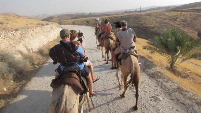 Al Jazeera is not suggesting this photo or anyone in this image is linked to the subject of this article. This image shows tourists riding camels near Jerusalem [File: Brooke Lefferts/AP Photo]