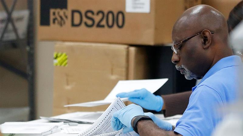 An employee at the Broward County Supervisor of Elections office examines ballots during a recount [Wilfredo Lee/AP Photo]