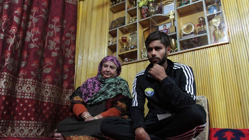 Footballer Farhan Ganai with his mother Rafiqa Banoo, who says it is 'not easy for our children to dream like people in other places' [Shuaib Bashir/Al Jazeera]