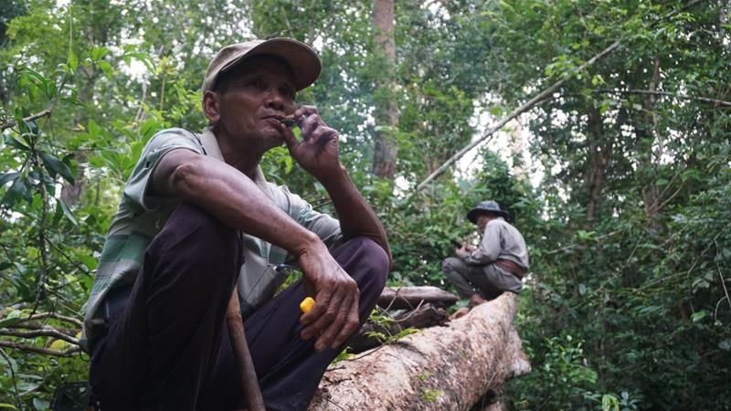 Lim, the leader of the 'vigilante' group comprising elderly men, smokes tobacco while waiting for team members to locate a nearby gang of loggers [Matt Blomberg/Al Jazeera]