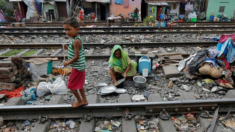 A boy walks past a woman cleaning her kitchen utensils between the railway tracks in a slum area of Kolkata, India [Rupak De Chowdhuri/Reuters]