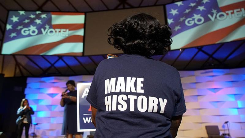 "A Stacey Abrams supporter wears a ""Make History"" shirt while listening to the gubernatorial candidate [File: Lawrence Bryant/Reuters]"