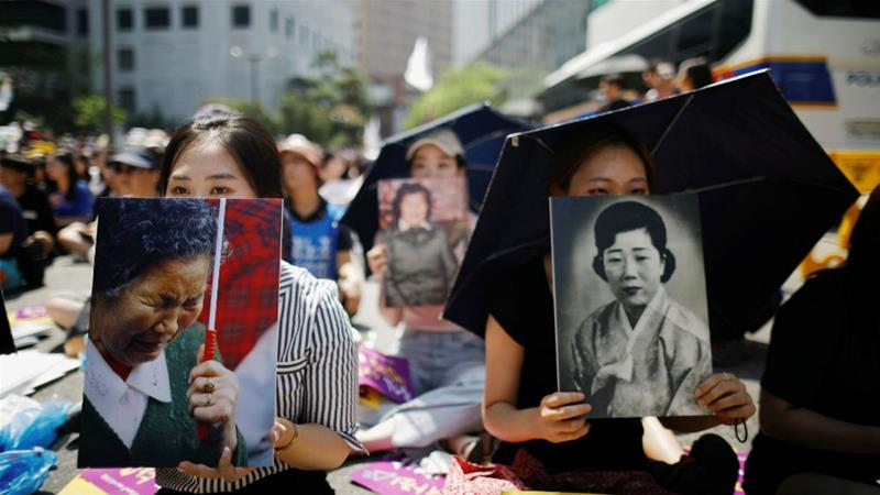 Women hold portraits of deceased former South Korean sex slaves during a weekly anti-Japan rally in Seoul [Kim Hong-Ji/Reuters]