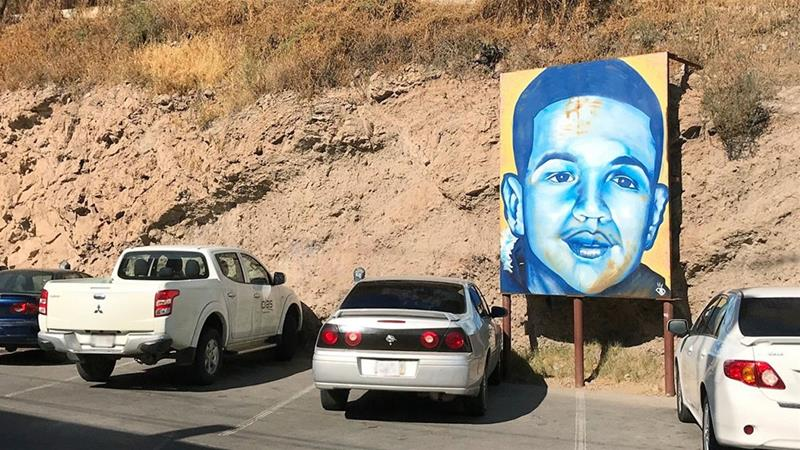 A portrait of 16-year-old Mexican youth Jose Antonio Elena Rodriguez, who was killed in Nogales, Mexico, is displayed on the Nogales street where he was killed that runs parallel with the US border [File: Anita Snow/AP Photo]