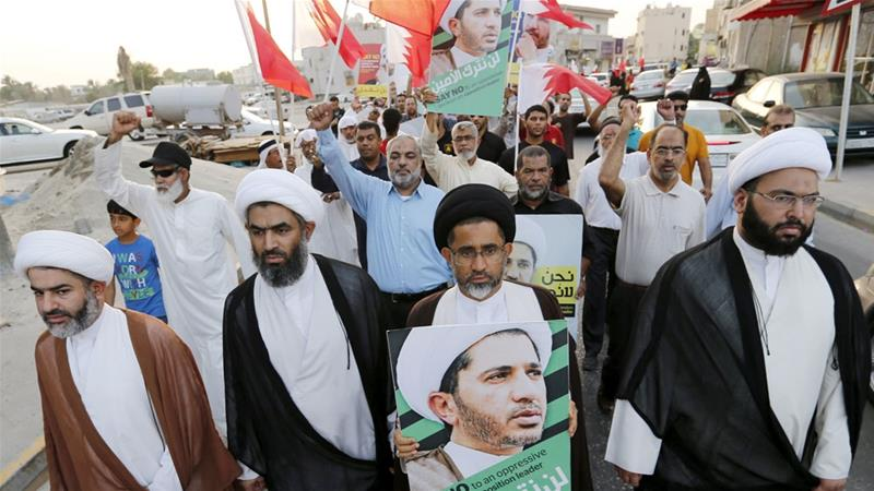 Protesters hold photos of Sheikh Ali Salman, Bahrain's main opposition leader who sentenced to life in prison [File: Reuters]