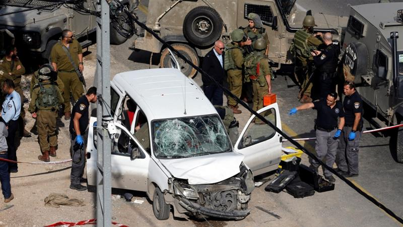Israeli policemen inspect the scene of an alleged car ramming attack near Hebron [Mussa Qawasma/Reuters]