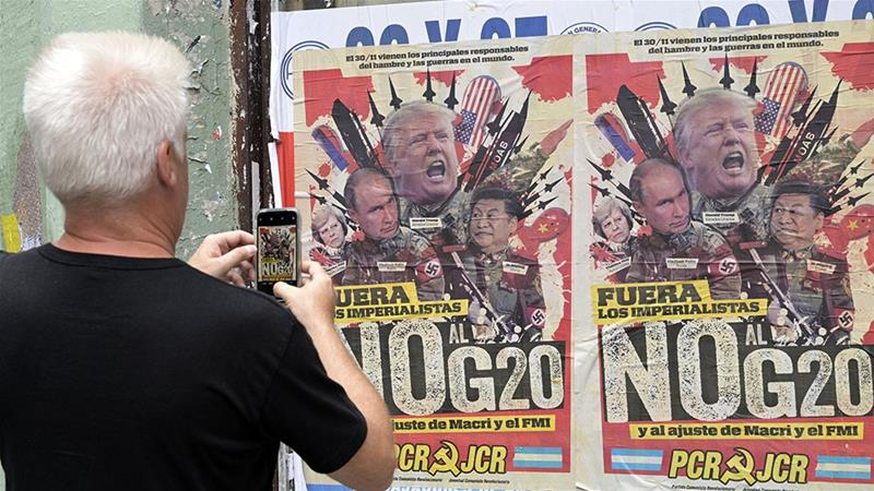 A passer-by takes a picture of an anti-G20 Summit banner in downtown Buenos Aires [Juan Mabromata/AFP]