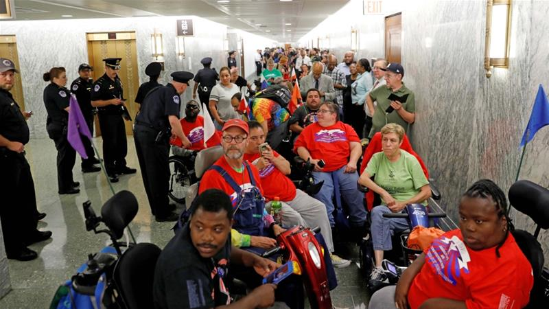 Disabled people protest in front of the Senate Finance Committee room hours before a hearing on the latest Republican effort to repeal Obamacare on September 25, 2017 [Reuters/Kevin Lamarque]