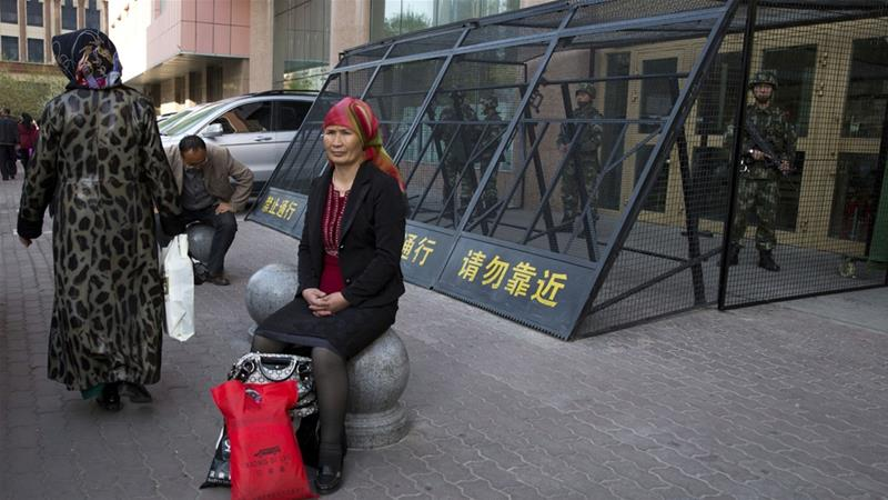 In this photo from 2014, an Uighur woman rests near a cage protecting heavily armed Chinese paramilitary policemen in Xinjiang [AP Photo/Ng Han Guan]