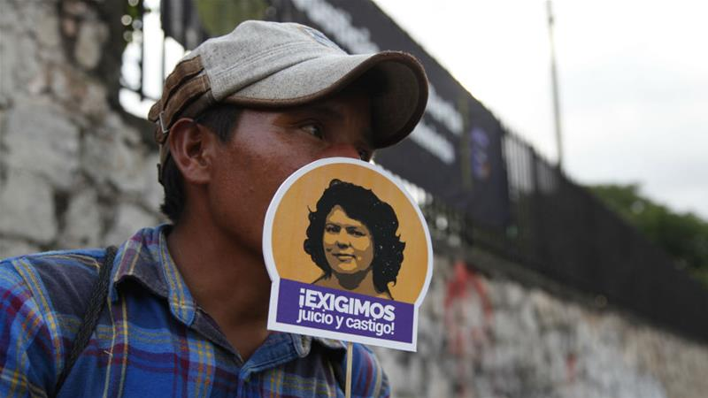A man holds a sign with the portrait of Caceres that reads 'We demand justice and punishment' [Fernando Antonio/AP]