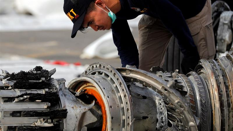 An official from Indonesia's transportation safety agency examines a turbine engine from the crashed Lion Air plane