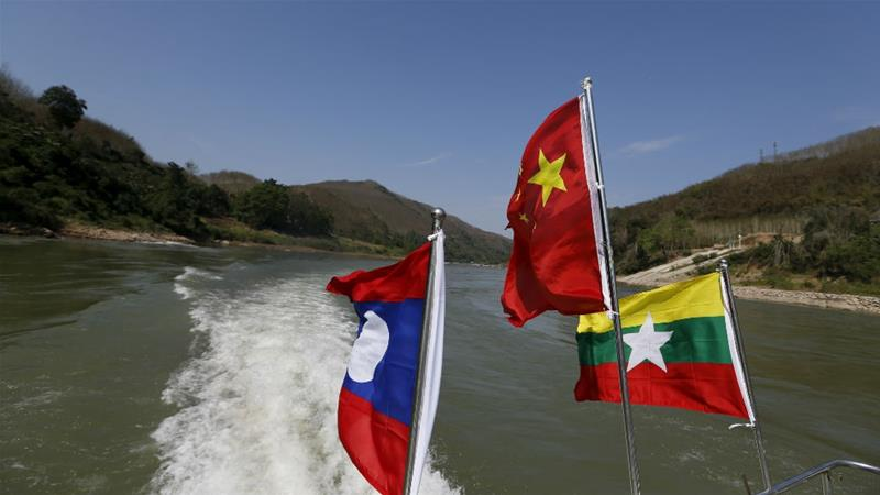 Flags of Thailand, China and Myanmar on the Mekong River in the border area known as the Golden Triangle [Jorge Silva/Reuters]
