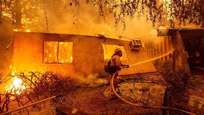 Firefighters battle flames at a burning apartment complex in Paradise, north of Sacramento, California [Josh Edelson/AFP]