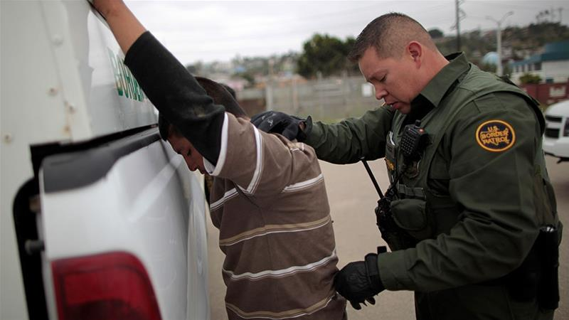 A United States border patrol agent pats down a man caught crossing from Mexico to the US [Lucy Nicholson/Reuters]