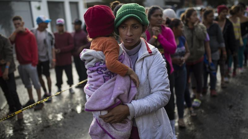 A woman holds her daughter while standing a line outside a migrant and refugee shelter in Tijuana [File: Rodrigo Abd/AP Photo]