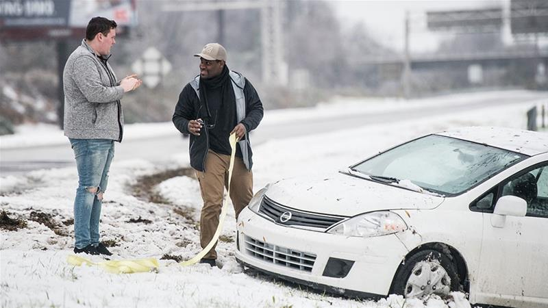Two men prepare to pull a vehicle out of the snow in Charlotte, North Carolina [Sean Rayford/Getty Images]