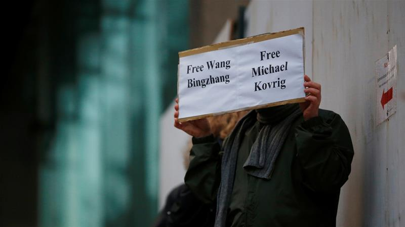 A man holds a sign calling on China to release Wang Bingzhang and former Canadian diplomat Michael Kovrig [Lindsey Wasson/Reuters]