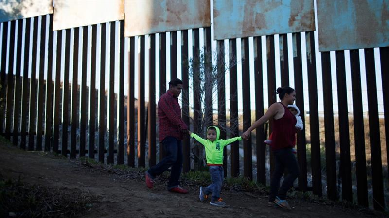 Central Americans walk next to the border fence in Tijuana, Mexico [Mohammed Salem/Reuters]