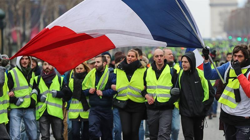 A protester in Paris wearing a yellow vest (gilet jaune) waves the French national flag during a demonstration against rising costs of living blamed on high taxes [File: Valery Hache/AFP]