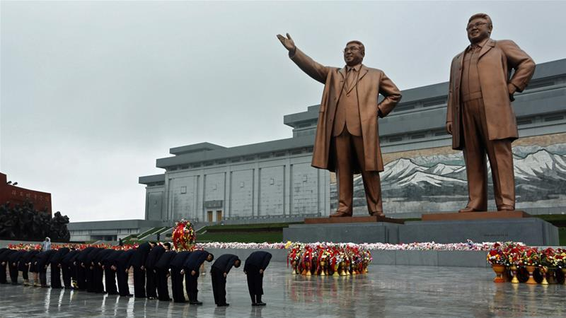 North Koreans pay tribute to the statues of late leaders Kim Il Sung, left, and Kim Jong Il, right [File: Vincent Yu/AP]