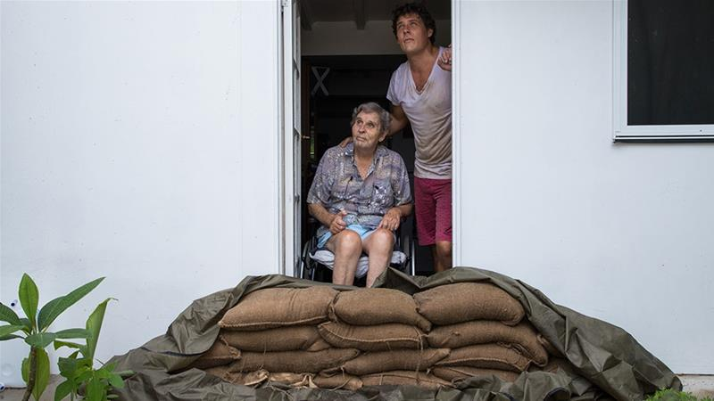 Parramatta Park resident John Irving and his son Steve Irving look at the sky from their sandbagged doorway in Cairns, Queensland, Australia [Marc McCormack/EPA]