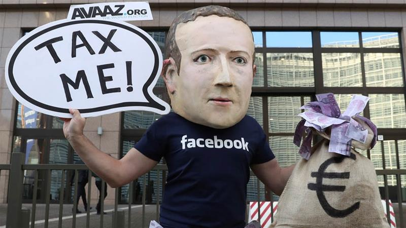 An activist wearing a mask depicting Facebook's CEO Mark Zuckerberg during a protest at the EU headquarters in Brussels [Yves Herman/Reuters]