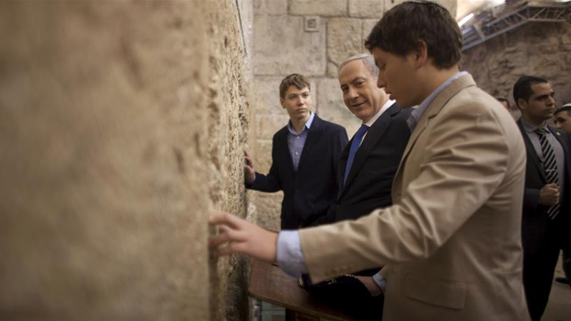 Israeli Prime Minister Benjamin Netanyahu, centre, with his sons Yair, background, and Avner, right, at the Western Wall [File: Uriel Sinai/AP]