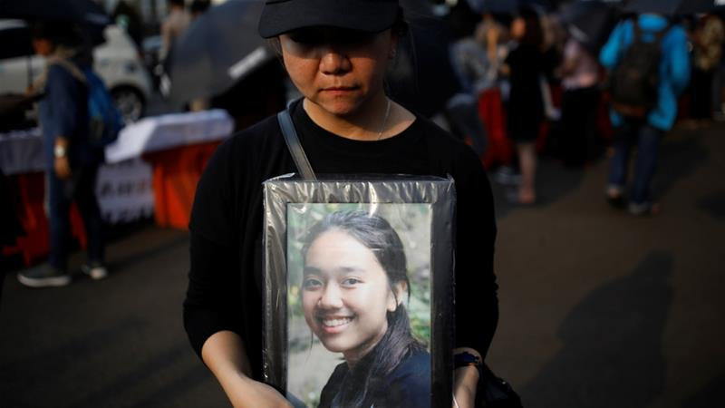 A woman holds a portrait picture of a relative killed in the Lion Air jet crash during a rally this month in Indonesia's capital, Jakarta [Darren Whiteside/Reuters]