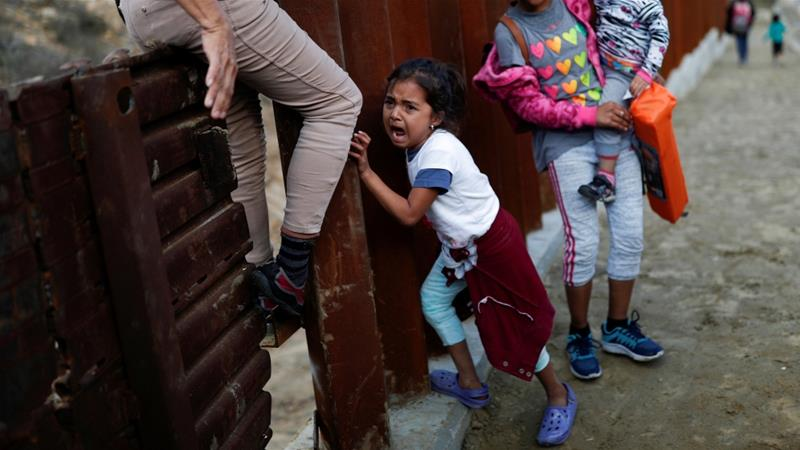 A migrant girl from Central America cries next to the border wall while she tries to cross with her family from Mexico to the US, in Tijuana, Mexico, December 11, 2018 [Carlos Garcia Rawlins/Reuters]