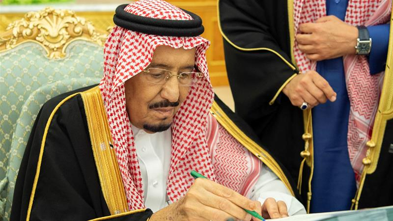 King Salman signs budget documents during a meeting in Riyadh on Tuesday [Bandar Algaloud/Saudi Royal Court]