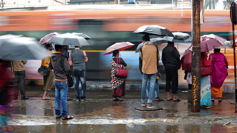 Commuters in Kolkata protect themselves from the heavy rain caused by the remnants of Cyclone Phethai [Piyal Adhikary/EPA]