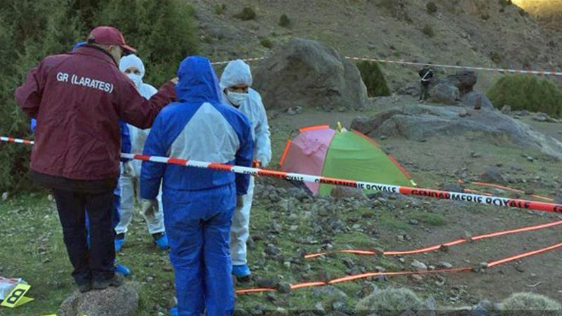 Police officers stand next to a tent at the scene where the bodies of two Scandinavian women were found [AFP]