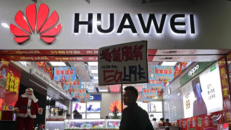 A worker holds a sign promoting a sale for Huawei 5G internet services in Shenzhen, China on Tuesday [Andy Wong/AP]