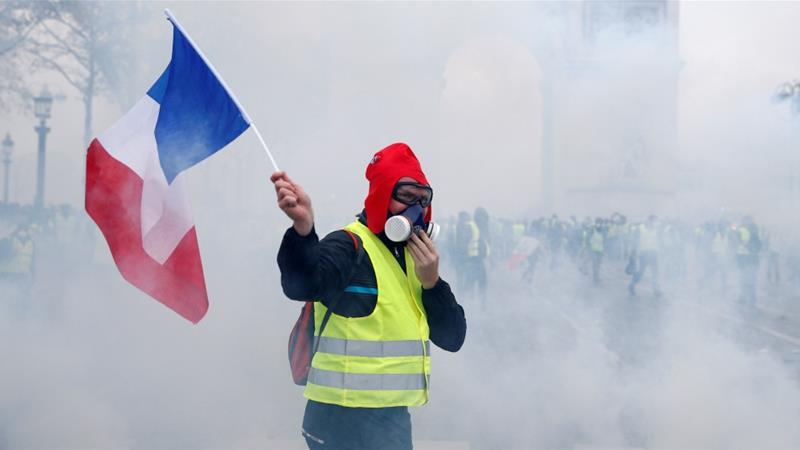 A protester wearing a yellow vest holds the French flag during clashes in Paris [Stephane Mahe/Reuters]